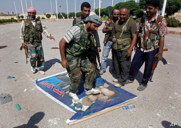 FILE - A Free Syrian Army fighter, center, steps on a poster depicting Syrian President Bashar al-Assad, at Tal Abyad, a Turkish-Syrian border crossing captured by the rebels, in eastern Syria, Sept. 22, 2012.
