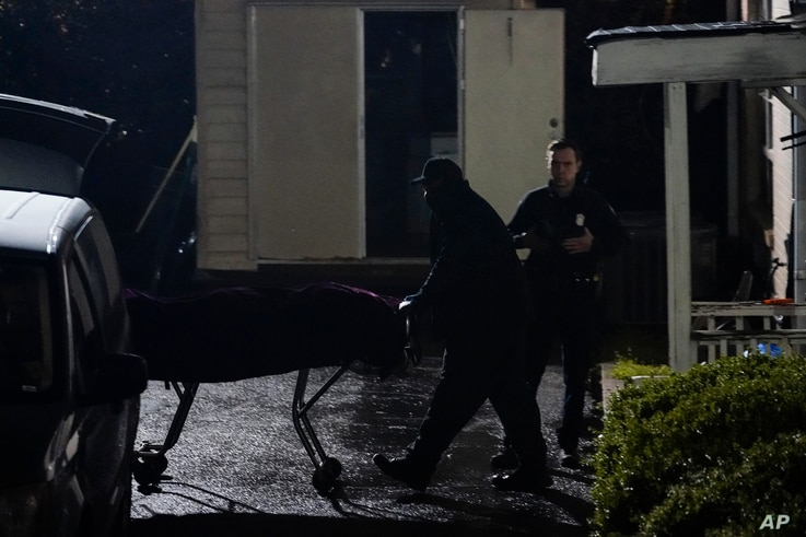 A body is removed from Gold Spa massage parlor after a shooting, late March 16, 2021, in Atlanta, Georgia.