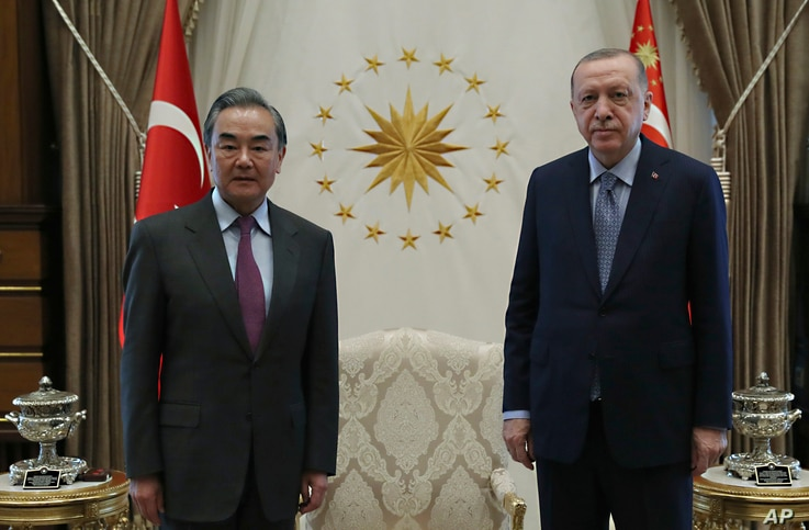 Turkey's President Recep Tayyip Erdogan, right, and Chinese Foreign Minister Wang Yi pose for a photo before a meeting, in Ankara, Turkey, March 25, 2021.