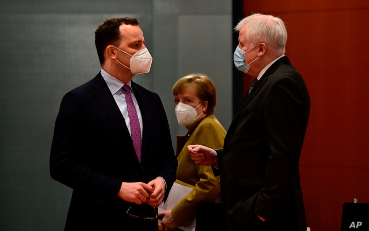 German Chancellor Angela Merkel, center, looks on as Health Minister Jens Spahn, left, and Interior Minister Horst Seehofer talk prior to the weekly cabinet meeting in Berlin, March 17, 2021.