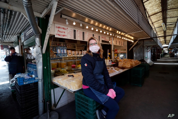 A vendor waits outside her stall at a deserted market in Budapest, Hungary, March 25, 2021.