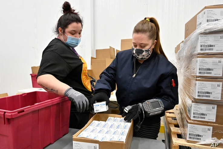 Employees with the McKesson Corporation scan a box of the Johnson & Johnson COVID-19 vaccine while filling an order at their shipping facility in Shepherdsville, Kentucky.