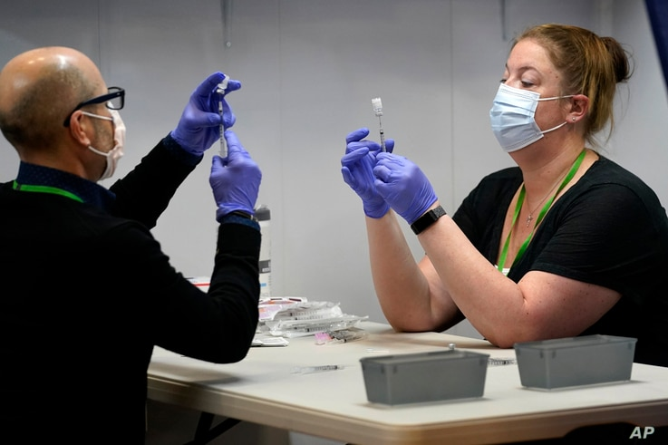 Pharmacy technicians fill syringes with a COVID-19 vaccine at an inoculation site in Portland, Maine, March 2, 2021.