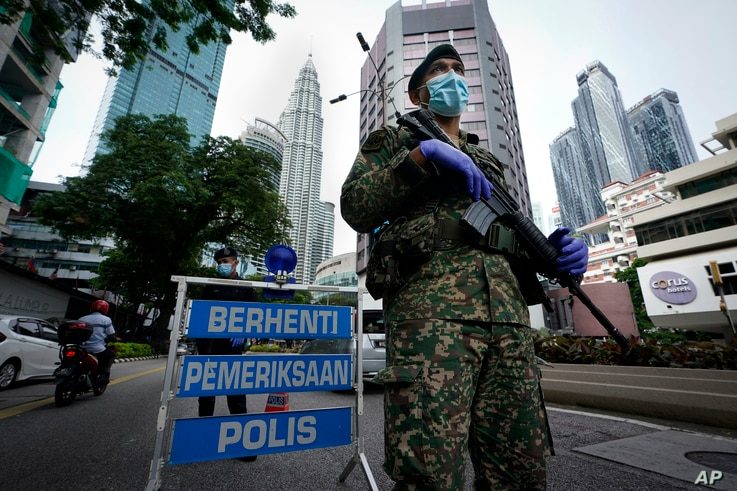 FILE - An armed soldier stands guard at a roadblock on the first day of a movement restrictions in downtown Kuala Lumpur, Malaysia, Jan. 13, 2021.