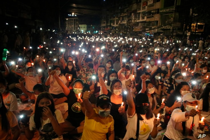 People participate in a candlelight night rally in Yangon, Myanmar, March 13, 2021.
