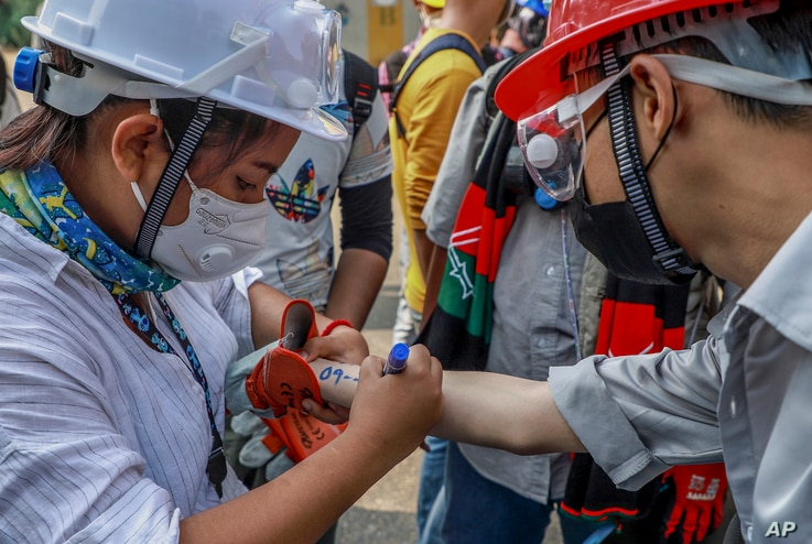 An anti-coup protester writes emergency information of another protester on his arm in Yangon, Myanmar, March 3, 2021.