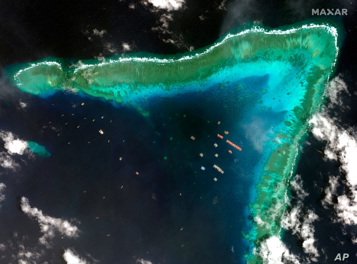 This satellite image provided by Maxar Technologies shows Chinese vessels at the Whitsun reef, in a disputed part of the South China Sea, March 23, 2021.
