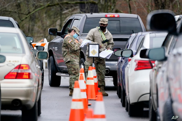 National Guard personnel check in people as they wait to receive a COVID-19 vaccination, Feb. 26, 2021, in Shelbyville, Tennessee.
