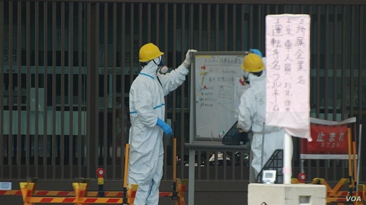 FILE - Security guards are seen at one of exterior doors leading to the Fukushima Daiichi nuclear power plant.