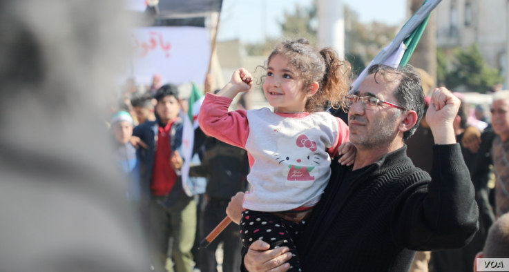 Anwar Alyousef and his daughter Tala, 4, at the protest on Feb. 26, 2021 in Idlib, Syria (VOA/Mohammad Daboul)