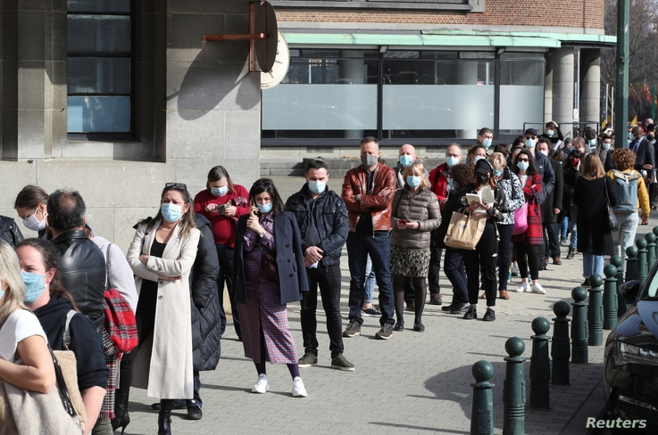 FILE - People queue outside a COVID-19 vaccination center in Brussels, Belgium, March 3, 2021.