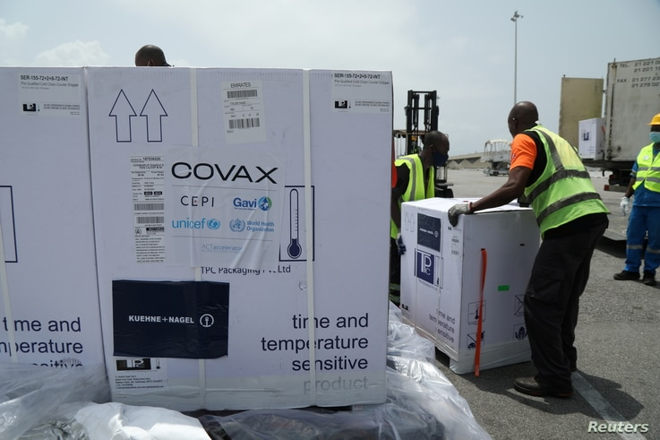 FILE - Workers offload boxes of COVID-19 vaccines distrubuted to lower-income countries under the COVAX initiative, in Abidjan, Ivory Coast, Feb. 26, 2021.