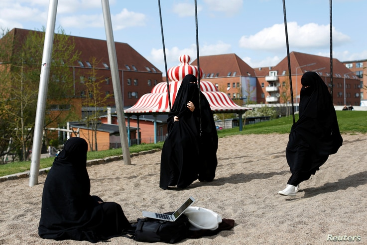 FILE - Young Muslim women in burqas chat on a playground in a park near Mjolnerparken, in Copenhagen, Denmark, May 3, 2018.