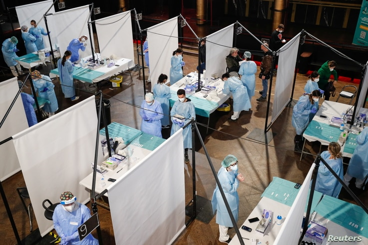 Health care workers prepare to collect coronavirus swab samples from concertgoers at the Palau Sant Jordi, in Barcelona, Spain, March 27, 2021.