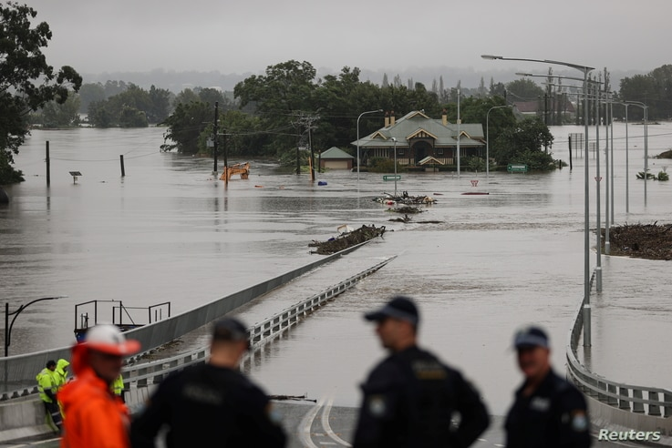 Police officers and road workers are seen in front of a submerged structure visible in floodwaters in the suburb of Windsor in Sydney, Australia, March 22, 2021.