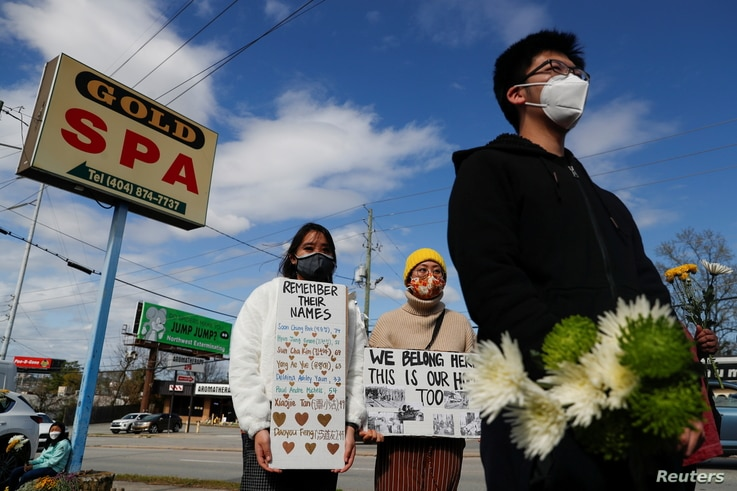 People hold placards during a vigil at a makeshift memorial outside the Gold Spa following the deadly shootings in Atlanta, Georgia, March 21, 2021.