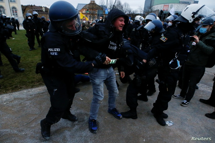 Police officers remove demonstrators from a square during a protest against the government's COVID-19 restrictions in Kassel, Germany, March 20, 2021.