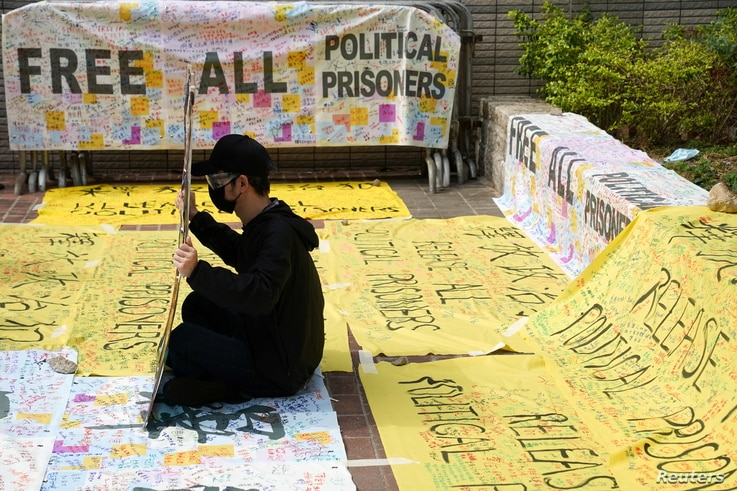 A supporter of pro-democracy activists holds a sign outside West Kowloon Magistrates' Courts where others queue up for a court hearing over charges related to national security, in Hong Kong, China.