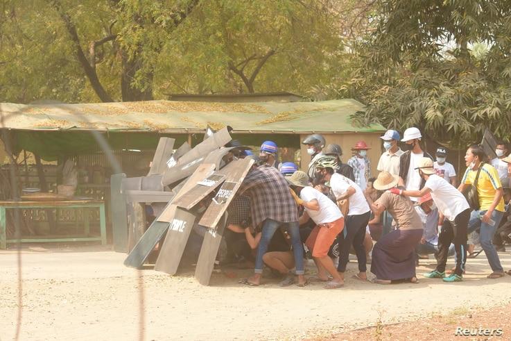 Protesters take cover behind shields in Nyaung-U, Myanmar, March 7, 2021, in this still image from a video obtained from social media.