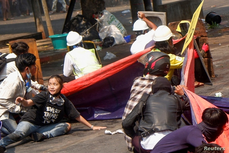 Protesters lie on the ground after police opened fire to disperse an anti-coup protest in Mandalay, Myanmar, March 3, 2021.