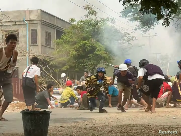 Protesters take cover during clashes with security forces in Monywa, Myanmar, March 21, 2021, in this still image from a video obtained by Reuters.
