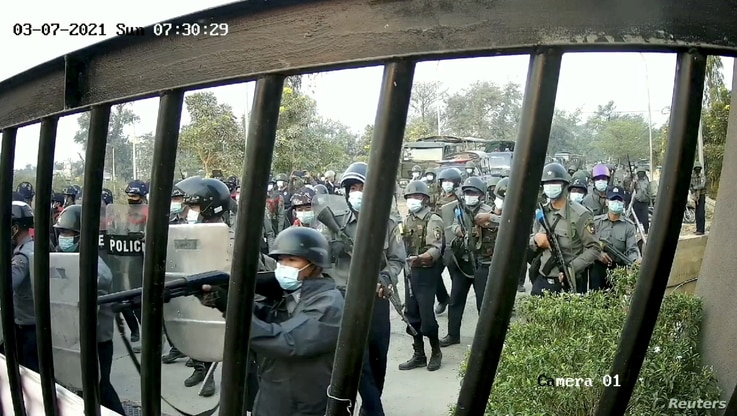 Riot police holding shields and guns march towards a gate of the Mandalay Technological University in Mandalay, Myanmar, March 7, 2021, in this still image obtained by Reuters from a CCTV footage.