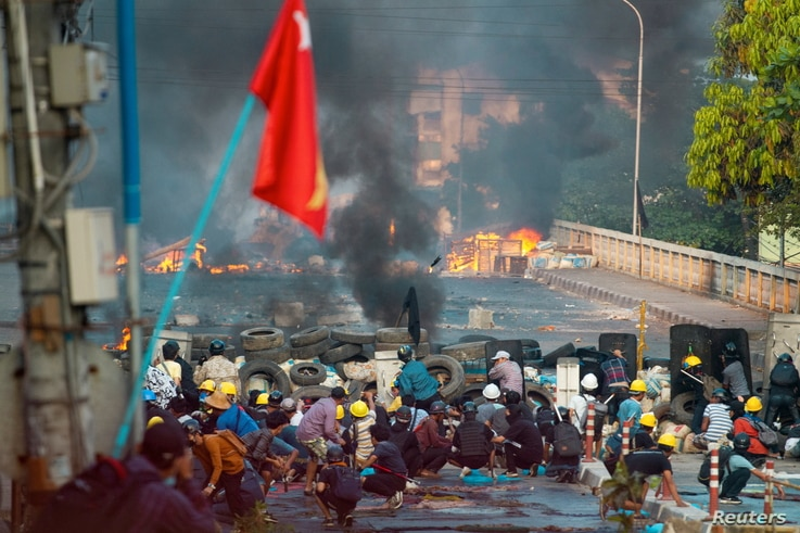 Anti-coup protesters take cover at a barricade as they clash with security forces on Bayint Naung Bridge in Mayangone, Yangon, Myanmar, March 16, 2021.