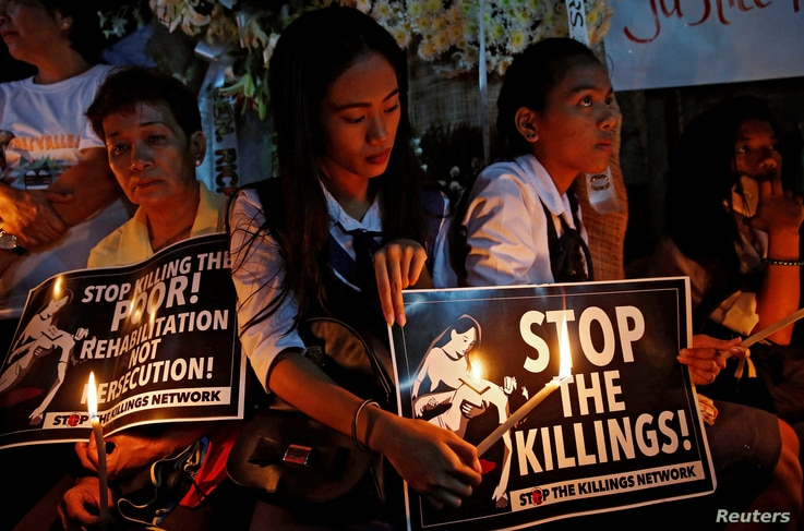 FILE - Protesters and residents hold lighted candles and placards at the wake of Kian Loyd delos Santos, a 17-year-old high school student, who was among the people shot dead in Caloocan city, Metro Manila, Philippines, Aug. 25, 2017.