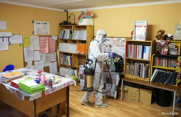 A worker disinfects a classroom at the Sibonile School for the Blind in Meyerton, South Africa, May 27, 2020, amid the spread of the COVID-19 outbreak.