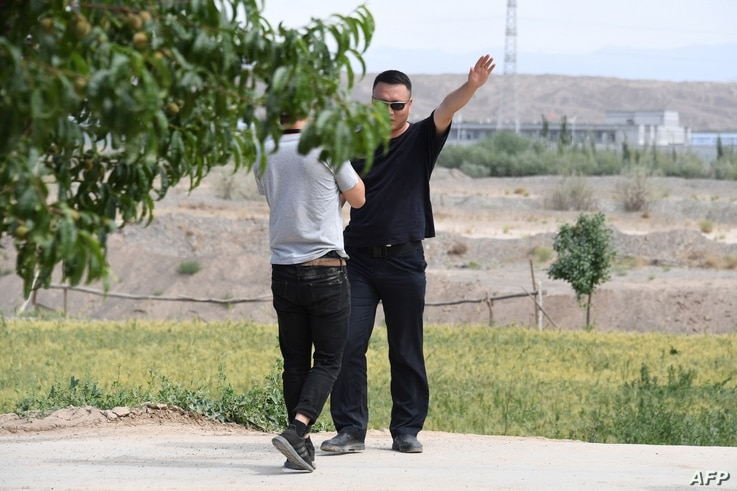 This photo taken on June 2, 2019 shows an AFP video journalist (L) being escorted away from a village while filming buildings…