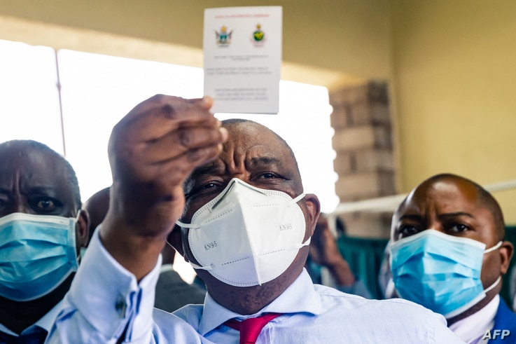 Zimbabwe vice president and Minister of Health Constantino Chiwenga holds up his vaccination certificate after receiving the…