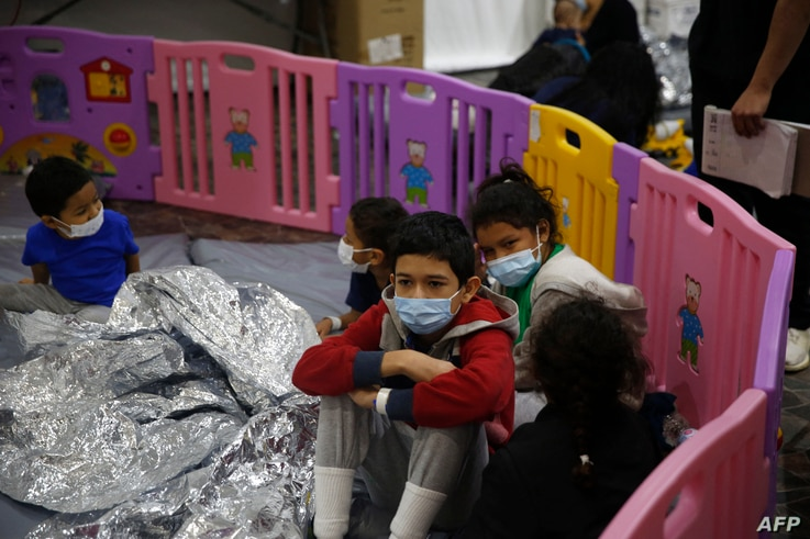Young unaccompanied migrants, ages 3-9 sit inside a playpen at the Donna Department of Homeland Security holding facility, the…