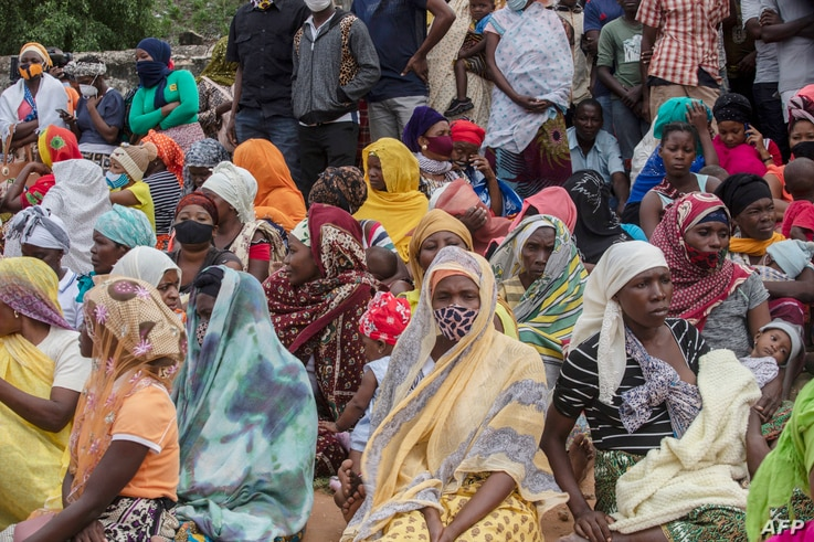 Families wait outside the port of Pemba on April 1, 2021, for the boat of evacuees from the coasts of Palma. - More than a...