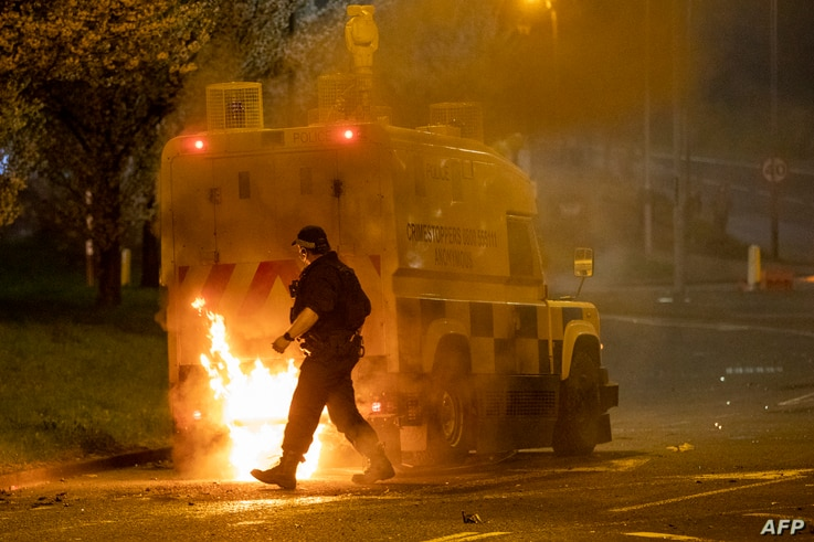 A police officer walks behind a police vehicle with flames leaping up the rear after violence broke out in Newtownabbey, north…