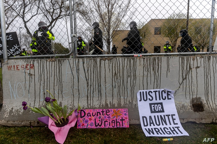 Flowers and signs are left in front of the security fence at the start of curfew to protest the death of Daunte Wright who was...