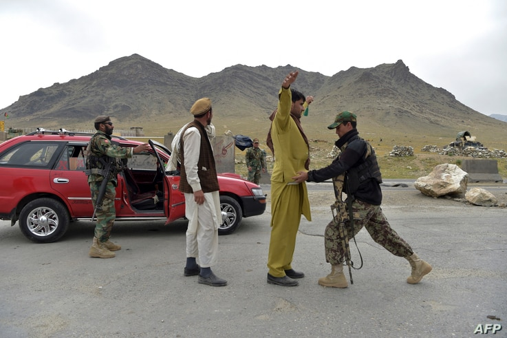 Afghan National Army (ANA) soldiers search men at a road checkpoint on the outskirts of Kabul on April 29, 2021. (Photo by…