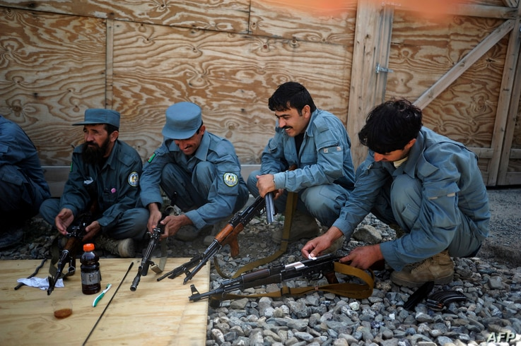 Members of the Afghan Police clean their rifles during a weapons maintenance training session at Narizah base in Narizah, …