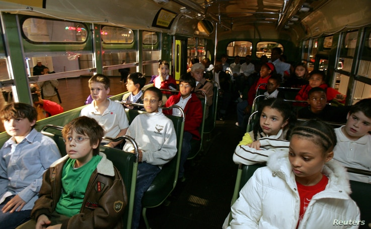 A multi-racial group of students sit next to each other on the actual bus where Rosa Parks, a black woman, refused to give up…