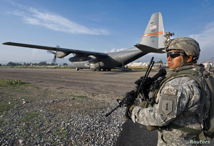 A member of the ISAF Security Forces secures the perimeter of a USAF C-130 cargo plane that carried U.S. Secretary of Defense…
