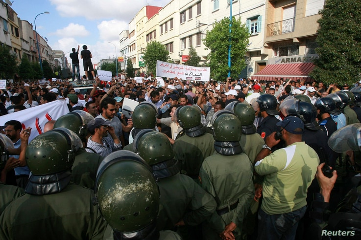 """Police face protesters pushing for democratic reforms during a rally organized by the country's so-called """"February 20"""" street…"""