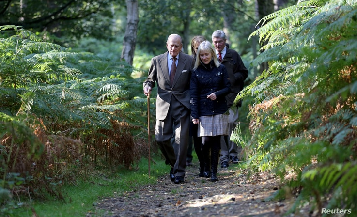 Britain's Prince Philip (L) is escorted during a visit to a 'The Conservation Volunteers' (TCV) conservation project at the…