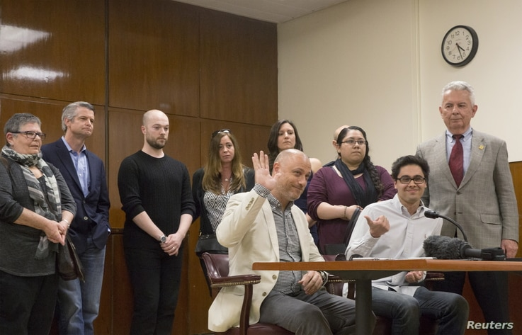 A juror raises his hand while speaking to the press at the state Supreme Court after the judge declared a mistrial in the case of murdered missing child Etan Patz, New York, May 8, 2015.