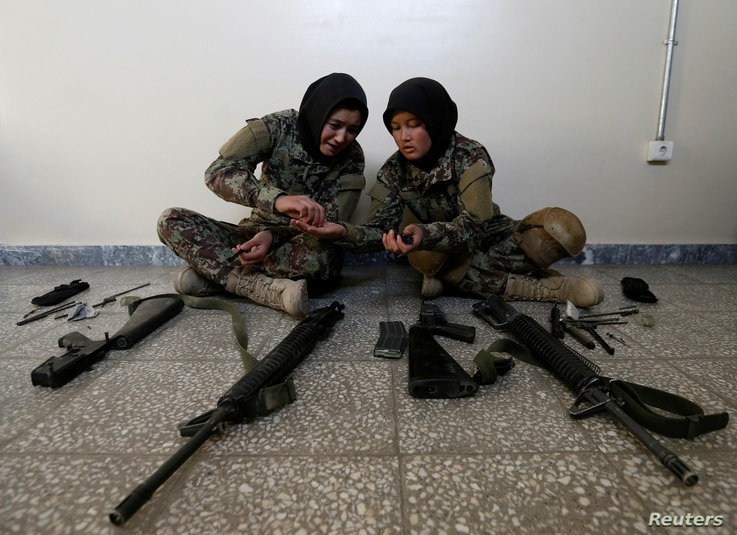 Female soldiers Karima Mohamadi, 21 (L), and Tamana, 19 (R), from the Afghan National Army (ANA) clean their weapons at the...