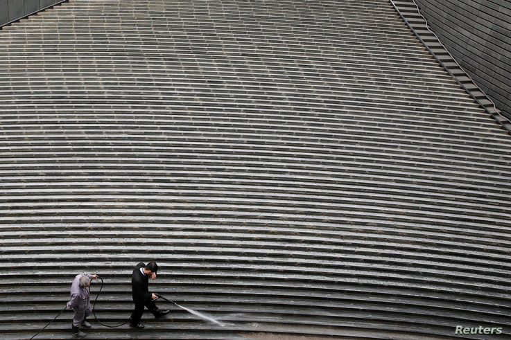 Workers clean steps near a recently erected office high-rise in Beijing, China April 20, 2017. REUTERS/Thomas Peter