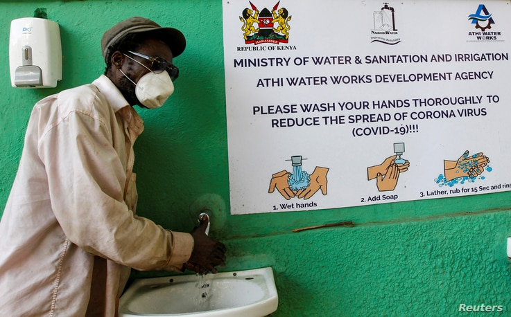 A man washes his hands with soap and water outside a retail market, amid concerns about the spread of coronavirus disease …
