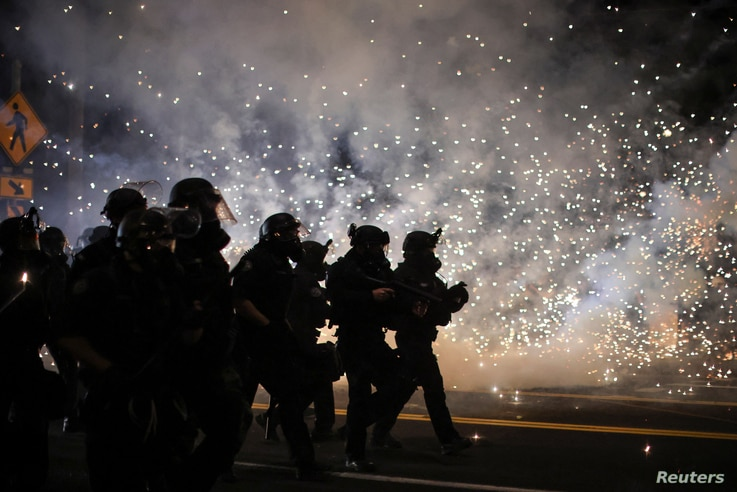 Police advance on protesters to clear a street on the 100th consecutive night of protests against police violence and racial...