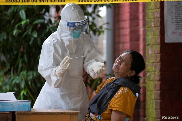 A woman reacts while getting a coronavirus swab test by medical staff at a quarantine centre amid the COVID-19 outbreak in...