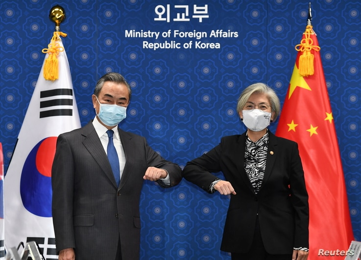 Chinese Foreign Minister Wang Yi (L) and South Korean Foreign Minister Kang Kyung-wha (R) greet prior to their meeting at the…