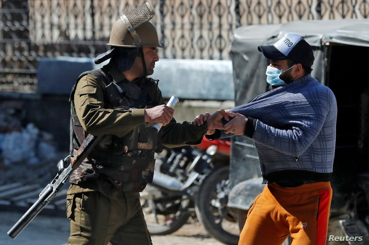 An Indian police officer detains a demonstrator during a protest after Friday prayers in Srinagar March 5, 2021. REUTERS/Danish…