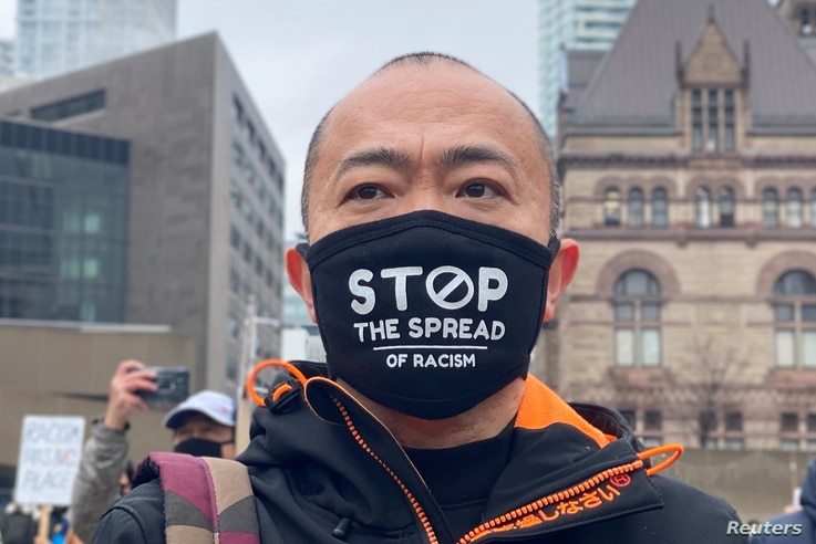 A man attends a protest against anti-Asian hate crimes, racism and vandalism, outside City Hall in Toronto, Ontario, Canada,…